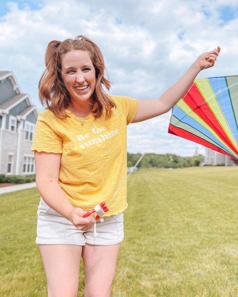Girl with a yellow shirt flies a kite to pay it forward